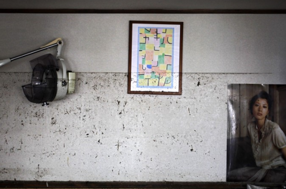 The waterline from the March 11 tsunami is left on the wall at the barber shop in Ishinomaki, Miyagi Prefecture, northeastern Japan on April 16, 2011. (AP Photo/Sergey Ponomarev)